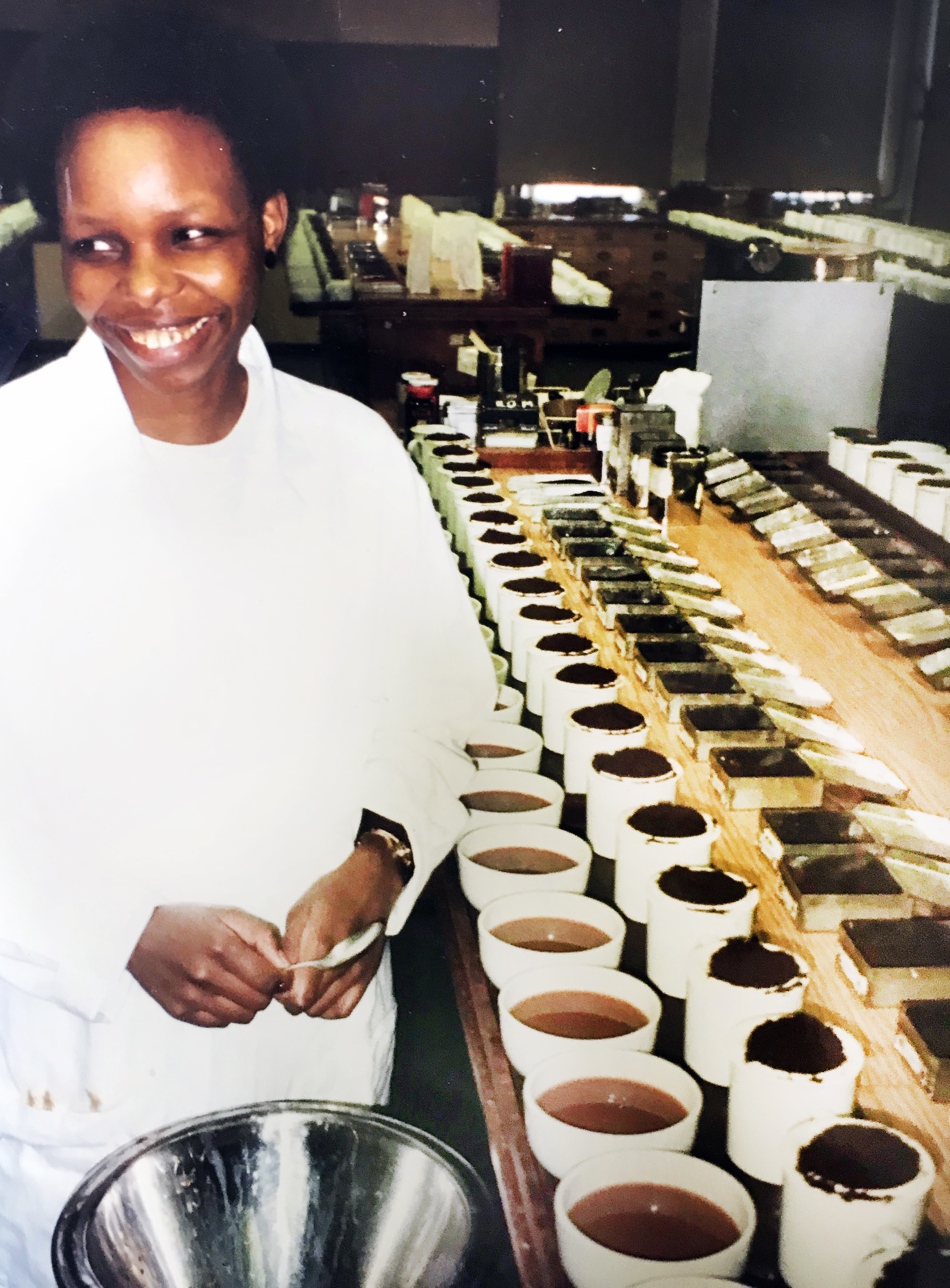 founder joyce maina in the 1990s smiling next to a large line of loose tea and cups of tea