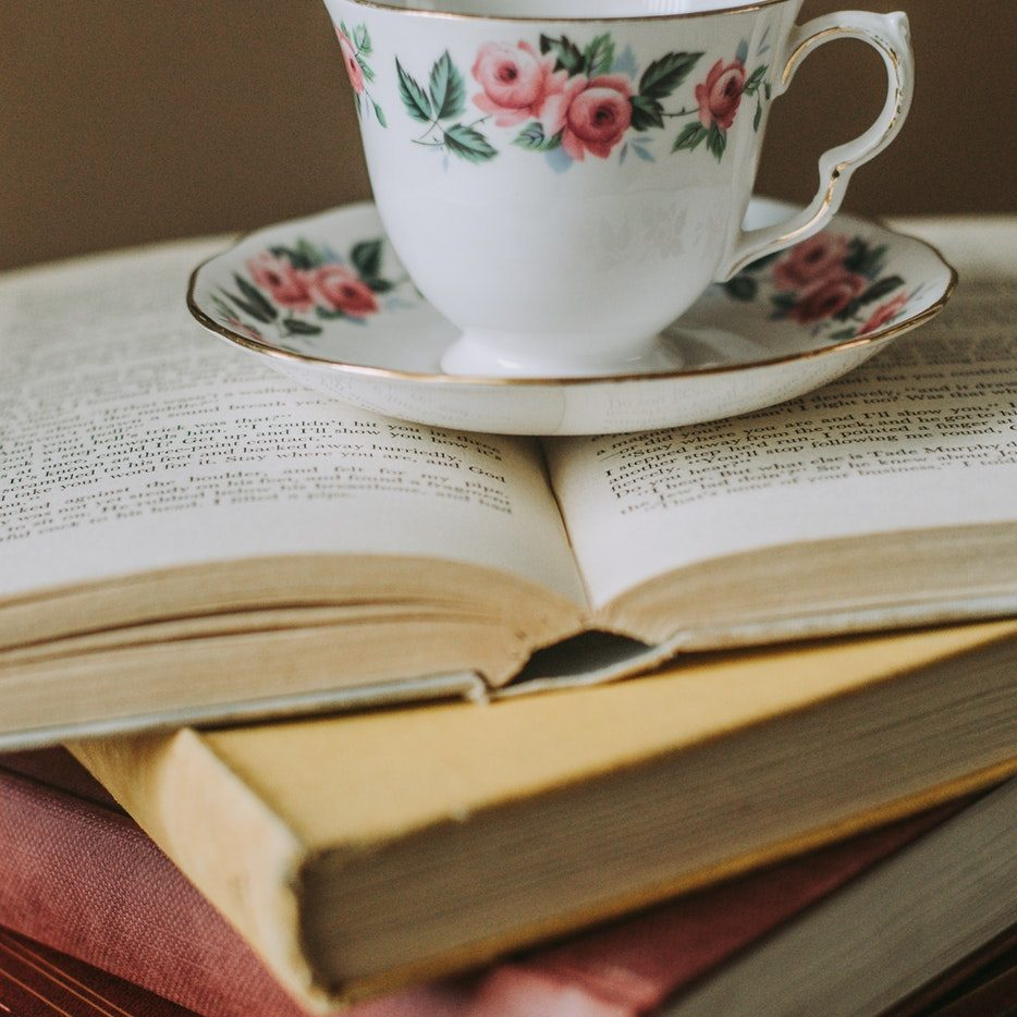 floral traditional tea cup and saucer on pile of old fashioned books