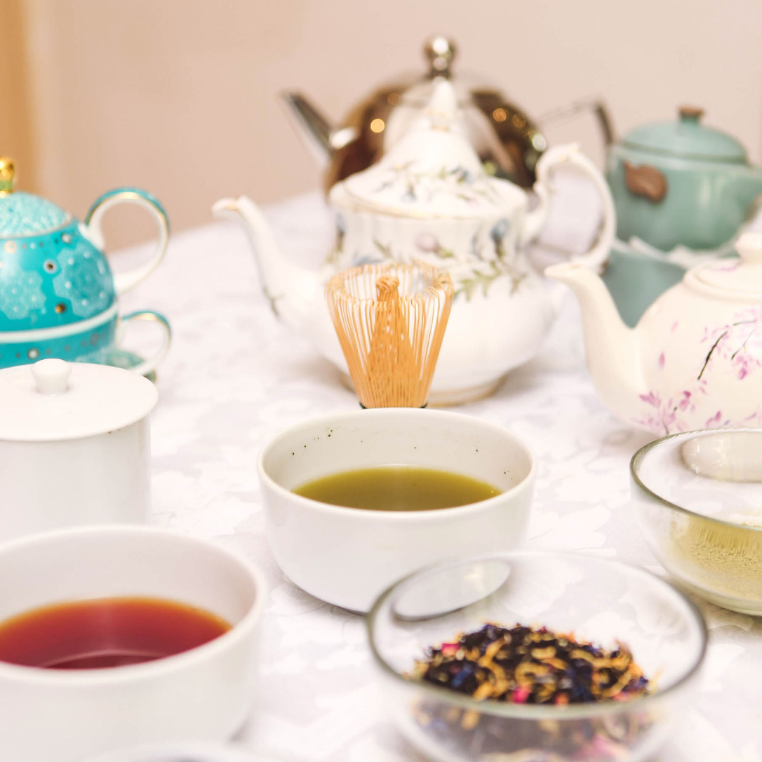 A range of tea paraphernalia including a bamboo tea whisk, loose tea, colourful cups of tea and teapots.