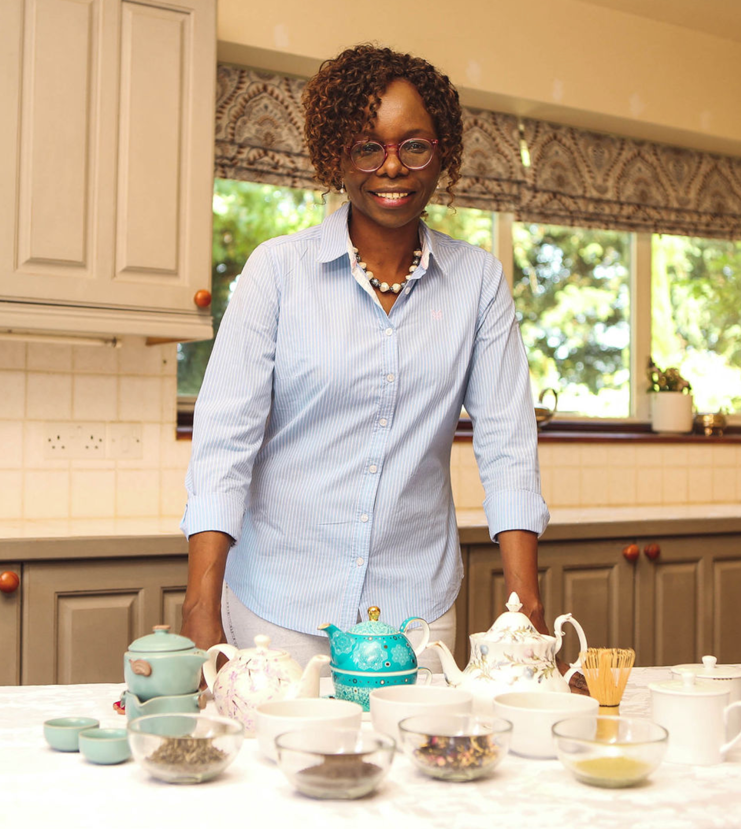 Founder and director Joyce Maina with tea accessories including teapots, loose tea and a tea whisk.