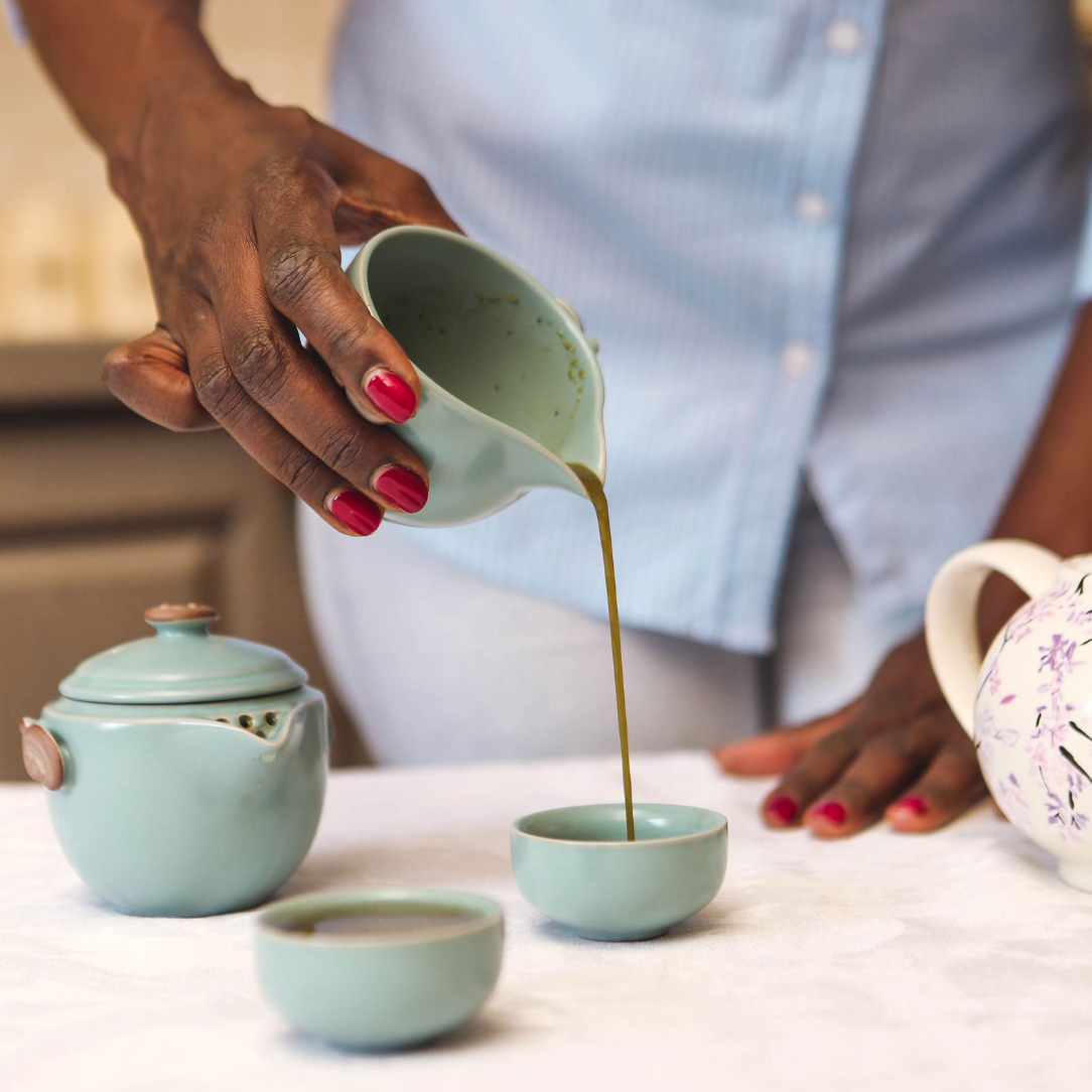 a woman's hand pouring tea from a cyan pouring cup.