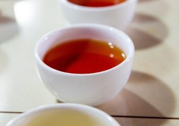 A line of different coloured teas in white cups on a white table